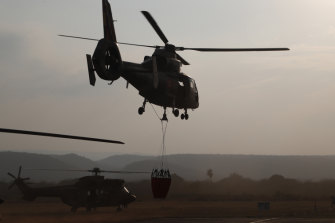 A helicopter lifts off from a military airport in Robore, Bolivia, with water to drop on the Chiquitanía Forest as the military fights forest fires on Sunday.