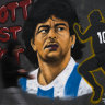 People walk in front of a mural by artist Eme Freethinker in honour of late Argentina soccer legend Diego Maradona in Berlin.