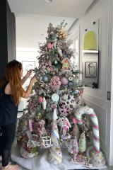 Understated: A Christmas stylist put the finishing touches to Roxy's outsourced Christmas tree, a confection of artificial confectionery.