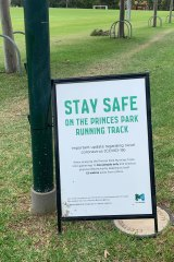 Signs in Prince Park reminding those using the running track to maintain social distancing.