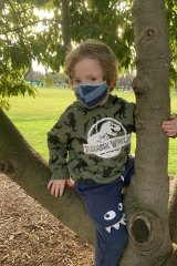 Griffin Williams, 5, sports a mask and the latest dinosaur gear.