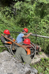 Men from a nearby village take a repaired pump back into one of the caves in the Tenglong complex.