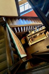 A Hogwart's style central staircase winds down to a heavily decorated surrealist piano.