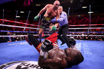 Fury stands over Wilder after a third-round knockdown.