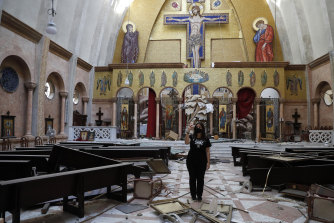 A woman takes pictures by her mobile phone for a damaged church.
