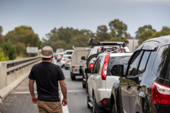 Nathan Goring looks on as a long queue of vehicles forms at the Victorian border near Albury.