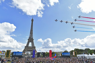 The elite aerial acrobatic team, Patrouille de France, perform behind the Eiffel Tower in Paris on Sunday to celebrate the handover of the Olympic flag to the city that will host the 2024 Games.