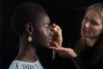 Makeup artist Kerry Tseros (right) applies eye embellishment to model Amer Athiu at the David Jones-Sephora beauty bar at Caulfield Racecourse.