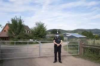 A police officer guards a farm in England where a COVID-19 cluster has occurred.