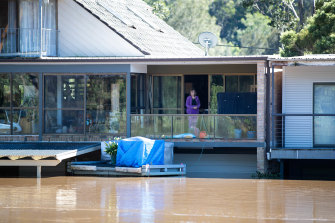 A woman watches the water from the top floor of her flood inundated house in Lower MacDonald.
