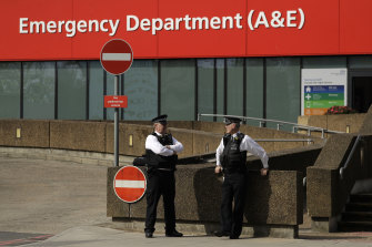Police officers stand outside St Thomas' Hospital, where Prime Minister Boris Johnson remains in intensive care.