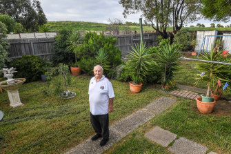 William Cartledge in his backyard, with the hill which was built on top of the Sunshine Landfills tip behind him.