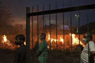 People watch burning funeral pyres of their relatives who died of COVID-19 in a ground that has been converted into a crematorium in New Delhi, India.