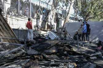 Migrants stand on a burnt container home in Moria refugee camp on Lesbos, Greece.