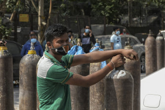 Family members of COVID-19 patients wait to refill their oxygen cylinders in New Delhi, India.