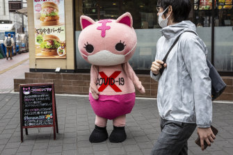 A costumed character reminds passersby in Tokyo of the dangers of COVID.