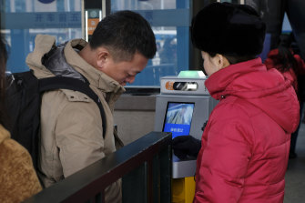 Facial recognition is widely used in China, like here, where Beijing commuters have their face scanned at the railway station.