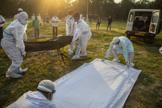 Municipal workers prepare to bury the body of a person who died of COVID-19 in Gauhati, India this week.