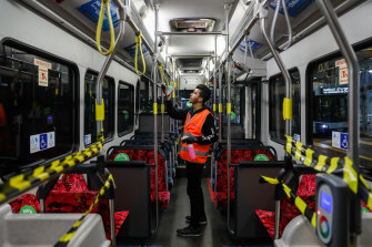 A cleaner disinfects a Sydney bus amid strict social distancing measures placed on the network.