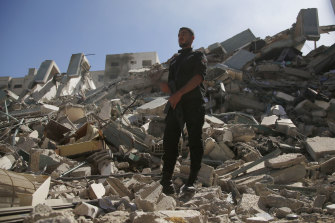 A policeman stands on rubble from a building housing AP office and other media in Gaza City that was destroyed after Israeli warplanes demolished it, Saturday, May 15, 2021.  The airstrike Saturday came roughly an hour after the Israeli military ordered people to evacuate the building.