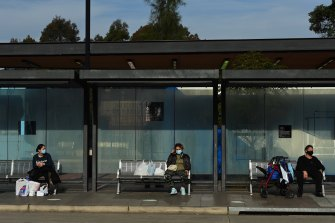 People wait for buses at Fairfield during Sydney's COVID-19 lockdown.