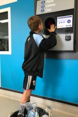 St Joseph's Corinda year 4 student Xavier Anderson recycles a container.