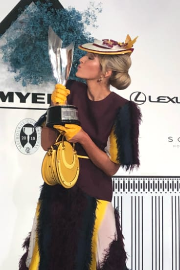From steel-cap boots to silverware ... Carle Rutledge kisses the winner's trophy after the Myer Fashions on the Field final on Oaks Day.