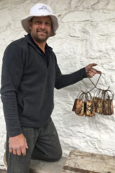 Andy Van der Wacht with the historic tags unearthed in the foundations of the Cobb & Co coach stables at The Sir George in Jugiong.