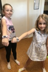 Mackenna (left) and Piper sporting their activity watches which tracks the coins they've earned.