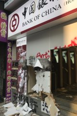 Protesters smashed the entrance to a Bank of China branch.