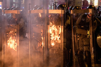 Riot police stand in front of a barricade set on fire by protesters after dispersing crowds outside the Mong Kok Police station in Hong Kong on Friday evening.