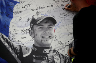 A man signs a remembrance board for Formula 2 driver Anthoine Hubert at the Belgian Grand Prix.