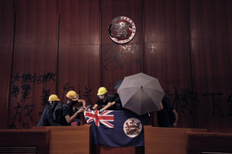 Protesters with a colonial-era flag storm Hong Kong's Legislative Council on July 1.