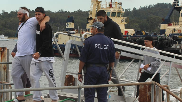 Male passengers are escorted off the cruise ship to waiting bus in Eden.