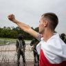 Gun-toting Belarus leader stands firm against mass rallies