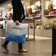 A customer holds a branded carrier bag inside a My Duty Free retail outlet at Munich airport in Munich, Germany, on Tuesday, Jan. 29, 2019. Deutsche Lufthansa AG has decided to speed up growth at Munich and develop it into a hub with a focus on Asia. Photographer: Michaela Handrek-Rehle/Bloomberg