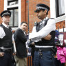 British police arrive and guard the Ecuadorian Embassy as protesters in support of Wikileaks founder Julian Assange protest outside.