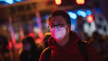 A Chinese man wears a protective mask as he arrives to board a train at Beijing railway station ahead of the Lunar New Year.
