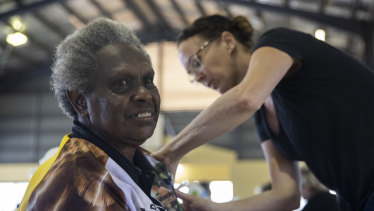 Rosie Gibuma receives a vaccination at the Boigu community centre from Queensland Health nurse Ruth Ferguson.
