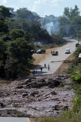 A road is blocked due to the collapsed dam, which has left 200 people missing.