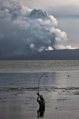 Although tens of thousands have evacuated the area, this resident continued fishing at Lake Taal in the shadow of the volcano.