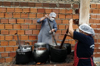 Walter Ferreira, left, and Laura Dure cook stew at a soup kitchen that feeds about 300 people daily in Luque, Paraguay. The UN World Food Program has warned more than 14 million people could go hungry in Latin America as the pandemic rages on.