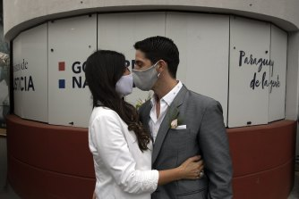 Bride Loris Sanchez and groom Manuel Soria, wearing protective face masks as a precaution against the spread of the new coronavirus, share a kiss before their wedding ceremony at the Civil Registry office, in Asuncion, Paraguay on Saturday, June 13.