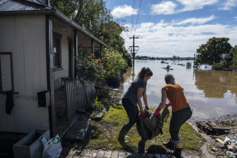 A friend helps Lisa Sullivan, right, carry a soggy pile outside.
