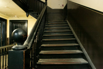 The original stairs remain copper-plated, worn and on a lean.