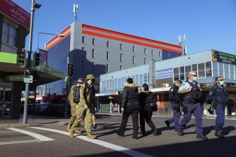 The ADF and NSW Police walking through Fairfield on Monday morning.