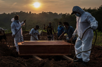 Grave diggers conduct a burial at a public cemetery for suspected COVID-19 victims in Semarang, Central Java.