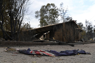 A charred Australian flag in front of a burnt-out home in Sarsfield, East Gippsland.