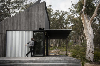 Simon Anderson closes up the house in four minutes, dropping the roof of the verandah and sliding across fire proof screens.