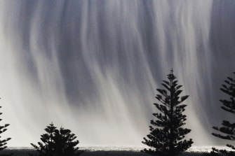 A rain curtain, backlit by sunshine, over parts of Sydney on Monday morning.